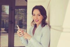 Femme heureuse avec le complexe de logement extérieur debout de sourire d'appartement de téléphone portable photographie stock