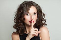 Femme heureuse avec le doigt près des lèvres, concept de silence images libres de droits