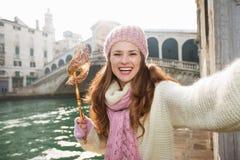 Femme heureuse avec le masque de Venise près du pont de Rialto prenant le selfie Images stock