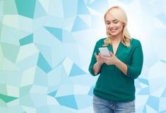 Femme heureuse avec le message textuel de smartphone photos libres de droits