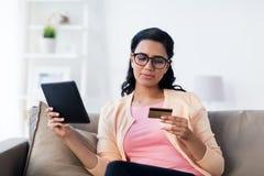 Femme heureuse avec le PC de comprimé et la carte de crédit à la maison Image stock