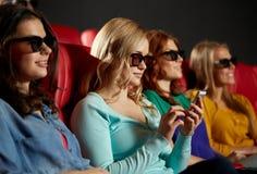 Femme heureuse avec le smartphone dans la salle de cinéma 3d Photographie stock libre de droits