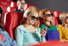 Femme heureuse avec le smartphone dans la salle de cinéma 3d Photos libres de droits