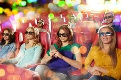 Femme heureuse avec le smartphone dans la salle de cinéma 3d Images stock