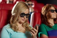 Femme heureuse avec le smartphone dans la salle de cinéma 3d Photo libre de droits