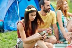 Femme heureuse avec le smartphone et les amis au camping Photos stock