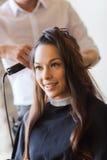 Femme heureuse avec le styliste faisant la coiffure au salon Photographie stock
