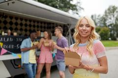 Femme heureuse avec le wok et les amis au camion de nourriture Image libre de droits
