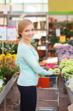 Femme heureuse avec les fleurs de achat de trollye d'achats Photographie stock