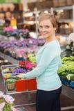 Femme heureuse avec les fleurs de achat de trollye d'achats Image libre de droits