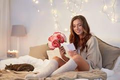 Femme heureuse avec les fleurs et la carte de voeux à la maison Images libres de droits