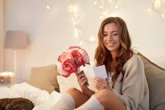 Femme heureuse avec les fleurs et la carte de voeux à la maison Photographie stock
