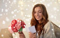 Femme heureuse avec les fleurs et la carte de voeux à la maison Photos stock