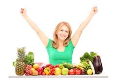 Femme heureuse avec les mains augmentées posant avec la pile des fruits et du veg Photographie stock libre de droits
