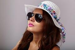 Femme heureuse avec les verres blancs de chapeau et de soleil Photographie stock libre de droits