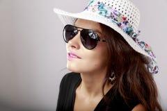 Femme heureuse avec les verres blancs de chapeau et de soleil Photographie stock