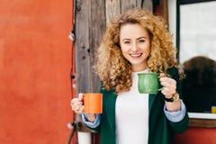 Femme heureuse avec les yeux bleus avec du charme de cheveux pelucheux bouclés blonds tenant deux tasses de café allant traiter s image stock