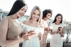 Femme heureuse avec plaisir regardant son smartphone d'amis Photo libre de droits
