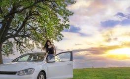 Femme heureuse avec sa voiture au coucher du soleil Image libre de droits