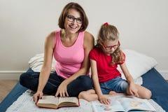 Femme heureuse avec son enfant de fille, lisant ensemble un livre a Image stock