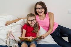 Femme heureuse avec son enfant de fille, lisant ensemble un livre a Photographie stock