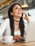 Femme heureuse ayant la conversation téléphonique de cellules tout en se reposant dedans Photos libres de droits