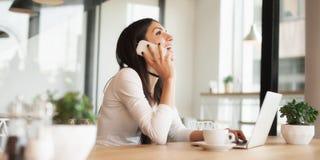 Femme heureuse ayant la conversation téléphonique de cellules tout en se reposant dedans Photo libre de droits