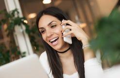 Femme heureuse ayant la conversation téléphonique de cellules tout en se reposant dedans Photographie stock