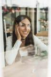 Femme heureuse ayant la conversation téléphonique de cellules tout en se reposant dedans Images libres de droits