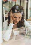 Femme heureuse ayant la conversation téléphonique de cellules tout en se reposant dedans Image stock
