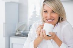 Femme heureuse ayant le café pendant le matin Photographie stock libre de droits