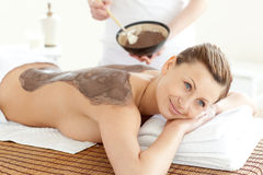 Femme heureuse bénéficiant d'une demande de règlement de peau de boue Images libres de droits
