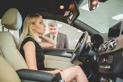 Femme heureuse bying la nouvelle électro voiture Photographie stock