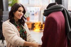 Femme heureuse choisissant des vêtements au magasin d'habillement Photos libres de droits