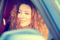 Femme heureuse conduisant dans la voiture le beau jour ensoleillé de voyage par la route Photographie stock
