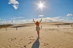 Femme heureuse contre des dunes de sable dans Leba, Pologne Images stock