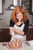Femme heureuse décorant le gâteau à la maison Image stock
