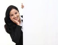 Femme heureuse d'affaires montrant l'enseigne vide image stock