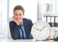Femme heureuse d'affaires montrant l'horloge Image stock