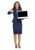 Femme heureuse d'affaires montrant à ordinateur portable l'écran vide et les pouces  Photos stock