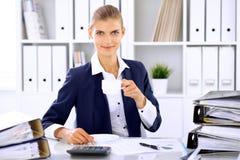 Femme heureuse d'affaires ou comptable féminin ayant quelques minutes pour le café et plaisir au lieu de travail Image stock