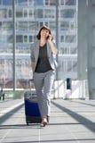 Femme heureuse d'affaires parlant au téléphone portable à l'aéroport Photographie stock libre de droits