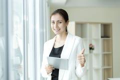 Femme heureuse d'affaires regardant la cam?ra avec le pouce de position  Concept r?ussi photo stock