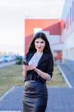 Femme heureuse d'affaires regardant le smartphone Photos stock