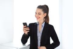 Femme heureuse d'affaires tenant le téléphone portable Images libres de droits