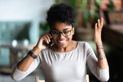 Femme heureuse d'Afro-américain excitée au sujet du bon conversati de téléphone image stock