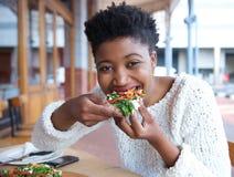 Femme heureuse d'afro-américain mangeant de la pizza Photos stock