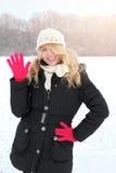 Femme heureuse d'hiver dans la neige regardant l'appareil-photo et l'ondulation photos stock