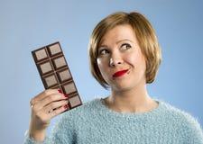 Femme heureuse d'intoxiqué de chocolat jugeant la grande bouche de barre expression enthousiaste souillée et folle de visage photos stock