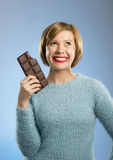 Femme heureuse d'intoxiqué de chocolat jugeant la grande bouche de barre expression enthousiaste souillée et folle de visage photographie stock